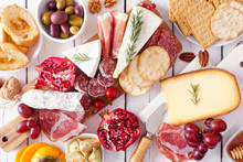 Charcuterie Board Of Assorted Cheeses, Meats And Appetizers. Top View Table Scene On A White Wood Background.