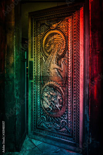 Photo  BALLINTOY HARBOUR, NORTHERN IRELAND, DECEMBER 20, 2018: Magnificent carved door with dragons and Dothraki horses, made with wood from the Dark Hedges