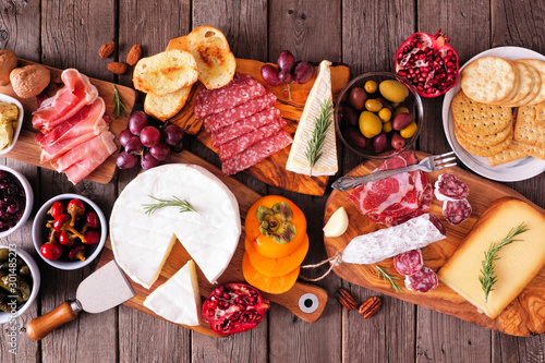 obraz PCV Charcuterie boards of assorted meats, cheeses and appetizers. Top view table scene on a rustic wood background.