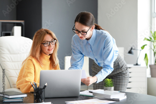 Obraz Mature businesswoman and her assistant working in office - fototapety do salonu