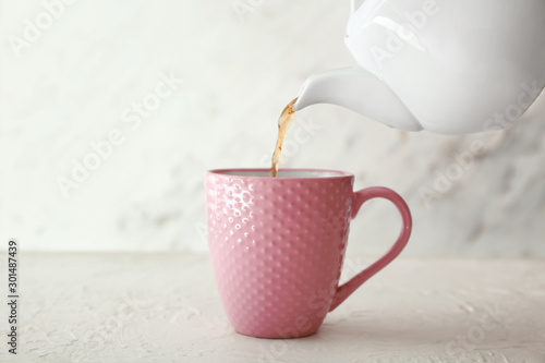 Tuinposter Thee Pouring of hot tea from teapot into cup on table