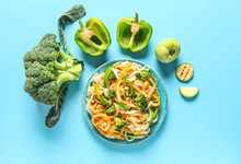 Plate With Tasty Pasta And Vegetables On Color Background