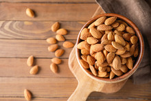 Bowl With Tasty Almonds On Woo...
