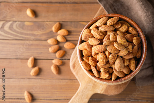 Photo Bowl with tasty almonds on wooden table
