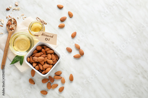 Tasty almond oil on white background Canvas Print