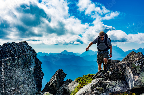 Adventurous man hiking on top of a mountain.