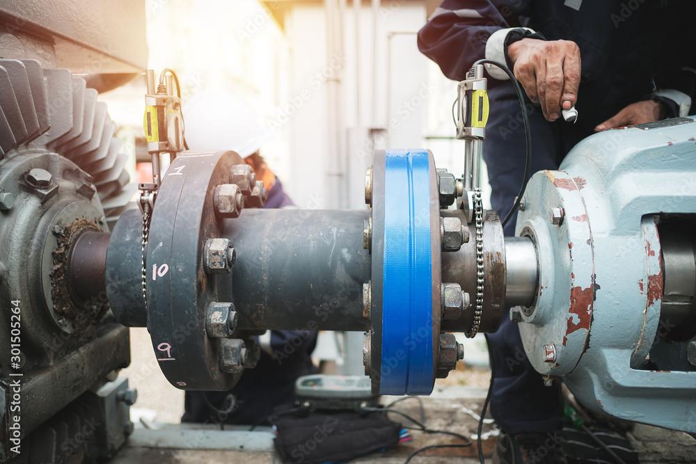 Fototapeta Technician inspector alignment pump  and electric motor, Repairing work in factory concept