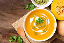 Butternut Squash Soup With Pumpkin Seed And Fresh Butternut Squash On Wooden Background