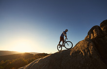 Silhouette Of Professional Bicyclist Balancing On Trial Bicycle On Top Of Big Boulder, Male Rider Making Acrobatic Stunt On Summer Evening, Blue Sky And Sunset On Background. Concept Of Extreme Sport