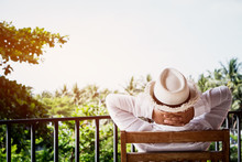 Back Side Of Senior Asian Woman Relaxing Or Enjoying Travel Vacation Travel On Wooden Chair At Balcony On Home Hotel, Looking Green View, Sitting Feel Thinking Something In Her Life