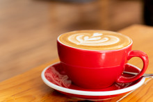 Cappuccino Coffee In Red Cup On Wooden Table