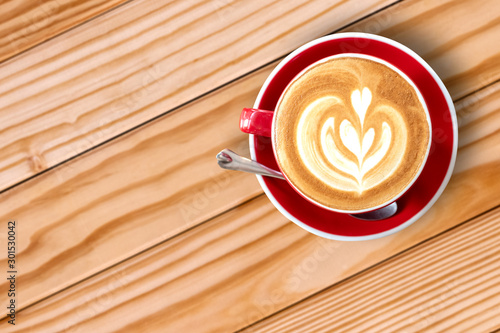 Wall Murals Cafe Top view of cappuccino coffee in red cup on wooden table