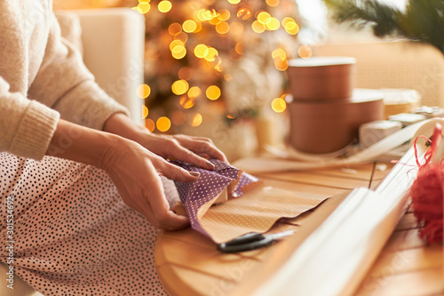 Christmas, festive mood and secret Santa tradition. Cropped image of mature female in sweater sitting on sofa in decorated living room with New Year's tree in background, wrapping gift. Focus on hands