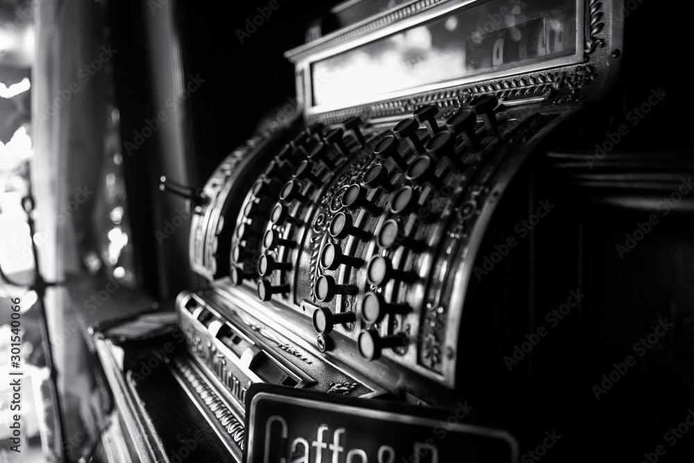 Fototapeta Black and white image of an old 19th century cash register. Selective focus on cashier buttons.