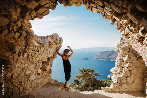 Obraz View from Monolithos, landscape at the island Rhodes, Greece. Girl admires the beauty of the landscape - fototapety do salonu