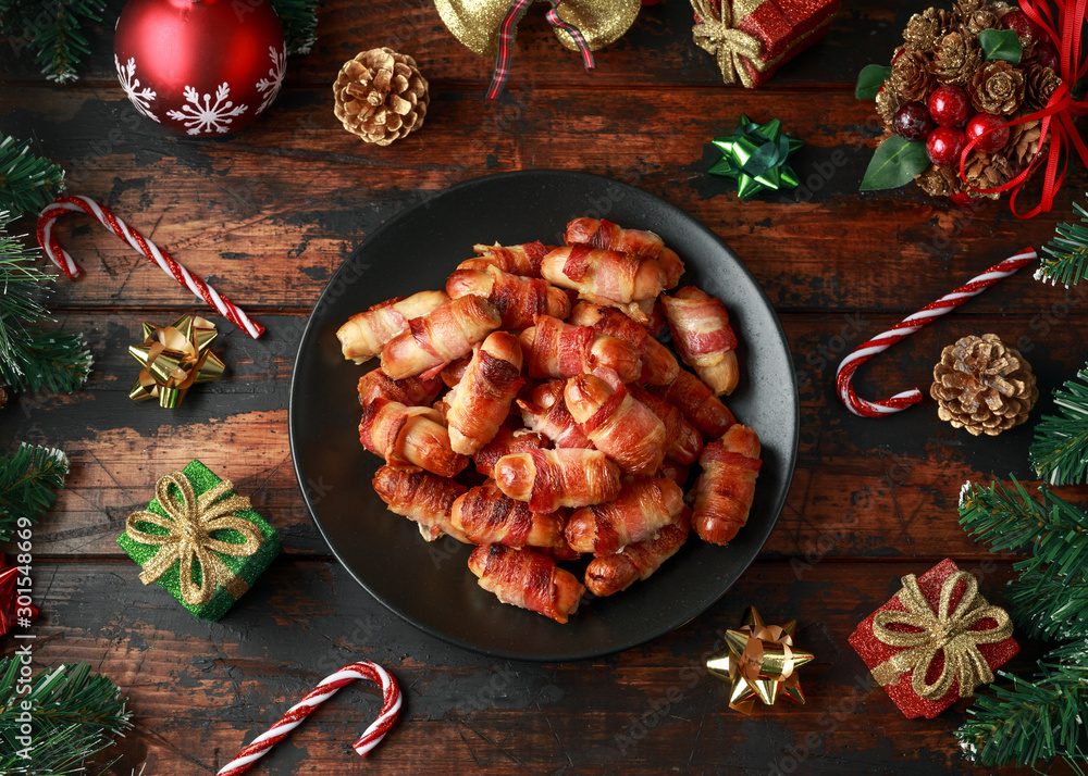 Fototapety, obrazy: Christmas Pigs in blankets, sausages wrapped in bacon with decoration, gifts, green tree branch on wooden rustic table
