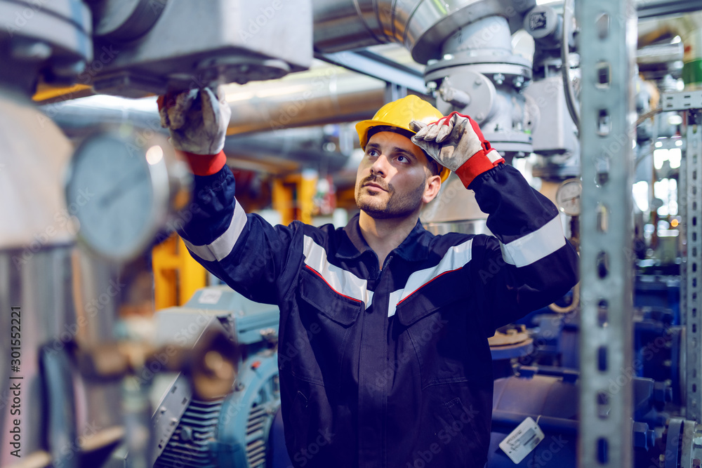 Fototapety, obrazy: Handsome Caucasian blue collar worker in protective uniform and with hardhat on head checking on boiler while standing in factory.