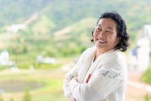 Asian Elderly Woman Wear A White Cloth Is Standing And Smiling In The Background Of Green Mountain Background, Concept Of Happy And Healthy Of Senior Asian People.