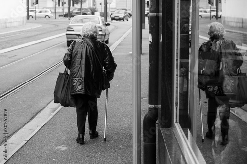 Fotografia  Portrait on back view of old woman xalking with stick in the street