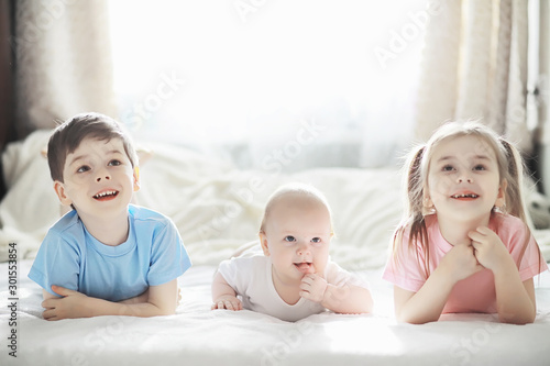 Children lie on the bed next to the newborn baby, little sister. Tablou Canvas