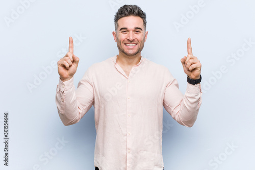 Fotografie, Obraz  Young handsome cool man indicates with both fore fingers up showing a blank space