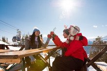 Group Of Friends Enjoying Hot Mulled Wine In Cafe At Ski Resort.