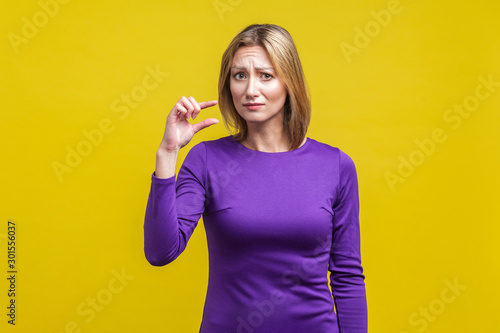 Vászonkép Portrait of disappointed woman in elegant purple dress frowning and showing a little bit gesture, asking some more, dissatisfied upset with amount