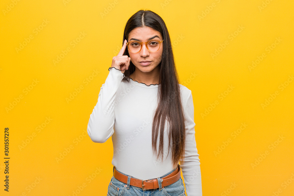 Fototapeta Young pretty arab woman against a yellow background pointing temple with finger, thinking, focused on a task.