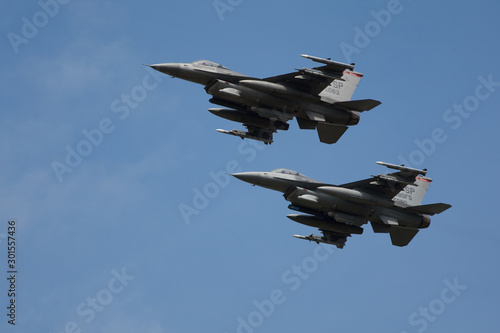 Canvas Print Two F16 Fast fighter jets fully loaded in formation flypast