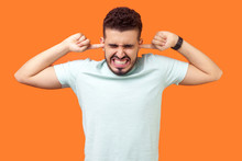 Don't Want To Listen Anymore. Portrait Of Brunette Man Standing With Irritated Grimace, Tightly Covering His Ears Not To Hear Annoying Loud Sound. Indoor Studio Shot Isolated On Orange Background