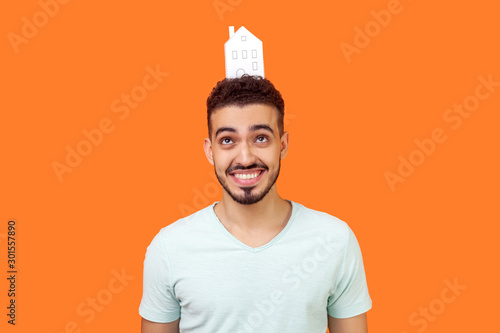 Obraz na plátně  Portrait of joyful young brunette man with beard in white t-shirt standing looking up at paper house on head and smiling, dreaming of home purchase