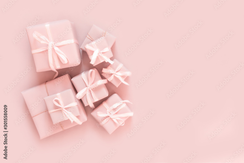 Fototapeta Christmas pink flat lay. Holiday boxes, fir branches on pink background. Christmas winter holiday congratulation invitation birthday wedding