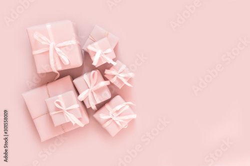 Christmas pink flat lay. Holiday boxes, fir branches on pink background. Christmas winter holiday congratulation invitation birthday wedding
