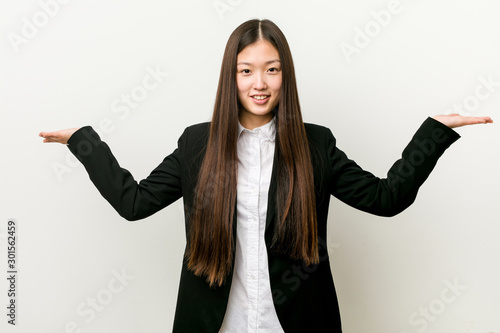 Fotomural  Young pretty chinese business woman makes scale with arms, feels happy and confident