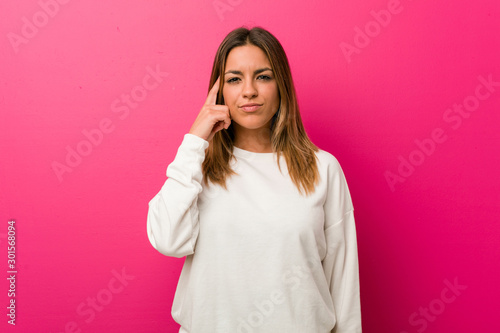 Fotografía  Young authentic charismatic real people woman against a wall pointing temple with finger, thinking, focused on a task