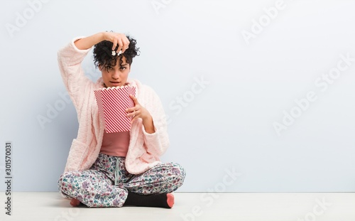 Fotografie, Obraz  Young african american woman sitting holding a popcorn box