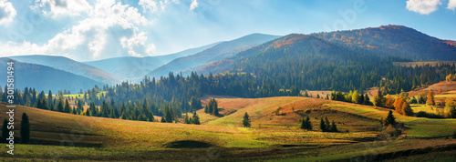 Fototapeta rural area of carpathian mountains in autumn. wonderful panorama of borzhava mountains in dappled light observed from podobovets village. agricultural fields on rolling hills near the spruce forest obraz