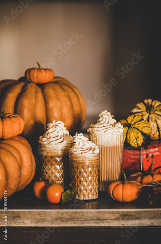 Pumpkin spice latte coffee drink topped with whipped cream and cinnamon in tall glasses among fresh pumpkins and persimmons over kitchen counter, copy space. Seasonal Autumn hot warming sweet drink