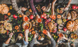 Family celebrating Thanksgiving day. Flat-lay of feasting peoples hands clinking glasses with rose wine over Friendsgiving table with Autumn food, roasted turkey and pumpkin pie over wooden table