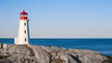 Peggys Cove lighthouse on a sunny day with blue sky.