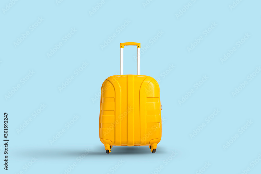 Fototapety, obrazy: Yellow suitcase on a blue background. Travel and vacation concept in triples. Flat lay, top view
