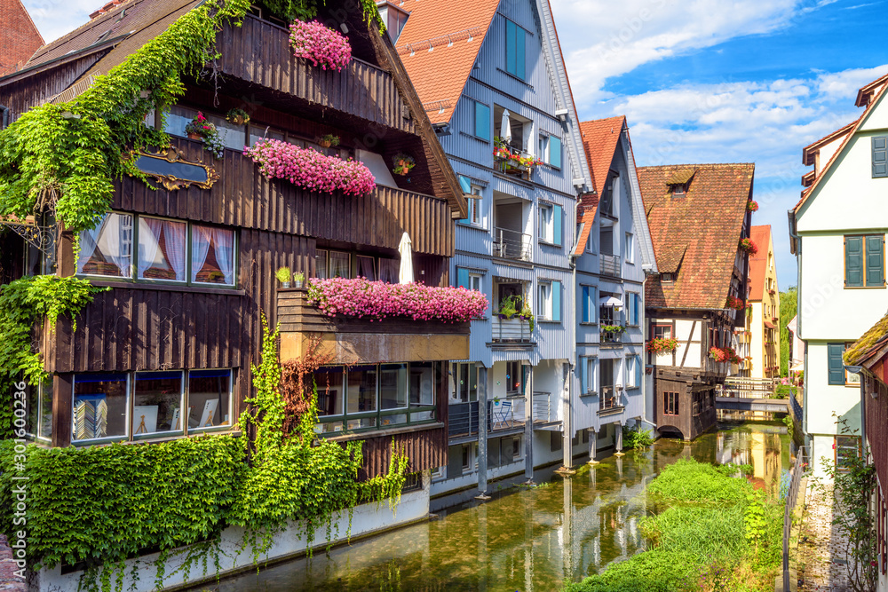 Fototapeta Vintage street with houses decorated by flowers in old town of Ulm, Germany. Nice view of historical Fisherman`s Quarter in summer. It is a landmark of Ulm. Ancient district of Ulm city with canals.