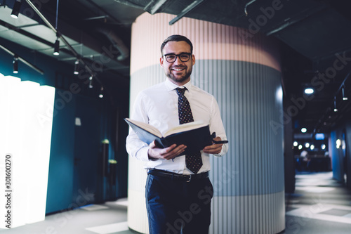 Half length portrait of cheerful accountant with textbook for planning feeling g Canvas-taulu