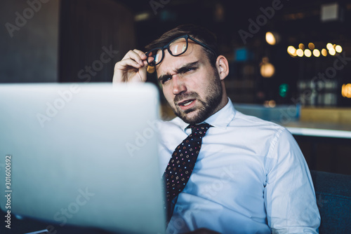 Puzzled businessman with angry expression on face confused with received email from employee with data information, unhappy male professional checking documentation via laptop computer using 4g