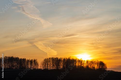 Spoed Fotobehang Oranje eclat Sunrise on a frosty autumn morning. Picturesque clouds on the orange sky.