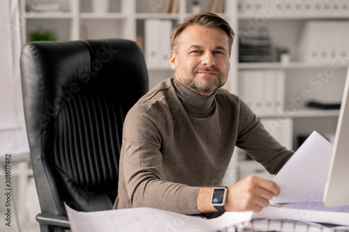 Canvastavla  Successful mature engineer with papers looking at you while in armchair by desk