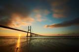Sun rising under the Vasco da Gama bridge in Lisbon, Portugal