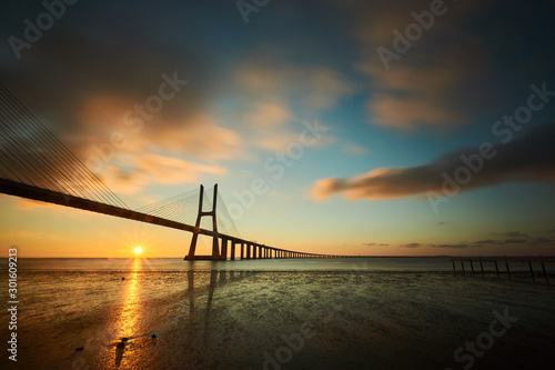 Sun rising under the Vasco da Gama bridge in Lisbon, Portugal Wallpaper Mural