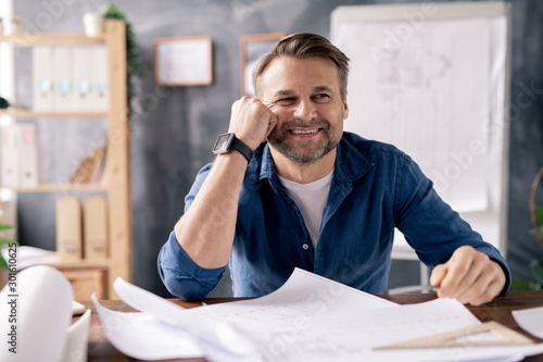 Fototapeta Smiling mature engineer sitting by table while working over new sketches obraz