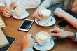 Hands of friends gathered by wooden table in cafe and having cappuccino